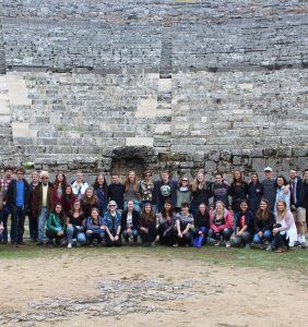 Group photo in front of the Ancient Theater of Dodoni, featuring one little golden 'pupper' to the bottom left.