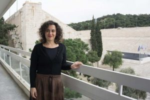 Portrait of Eleni standing on the CYA balcony with the Panathenaic Stadium in the background