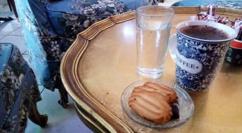 Some coffee and cookies on a golden table at Kekkos cafe